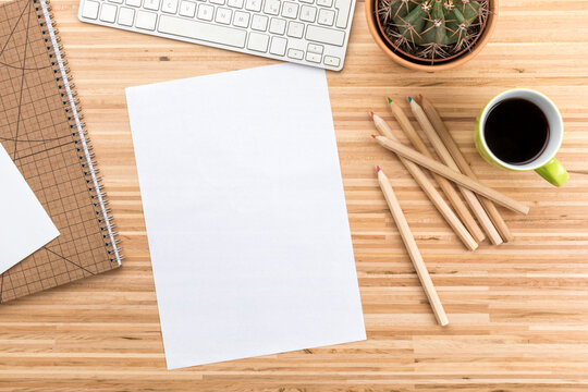 Designer wooden desk with computer keyboard, coffee cup, cactus,  stationery, color pencils  and copy space on blank paper