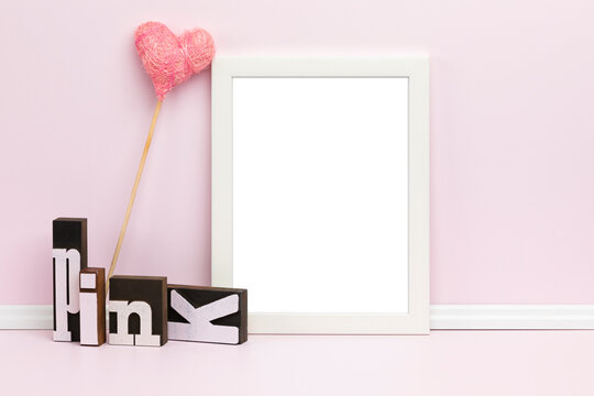 Feminine picture frame mockup. Template with white vertical frame, woodblock letters, heart-shaped ornament in front of pink wall. Blank image area masked with clipping path