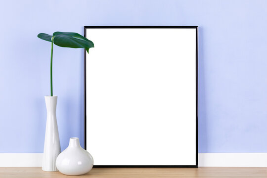 Elegant picture frame mockup with vertical black frame, vases and monstera leaf in front of purple wall. Blank image area masked with clipping path