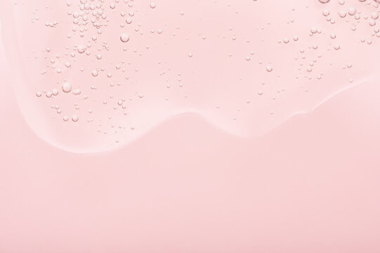 The texture of the gel, skincare serum on a pink background. A transparent liquid cosmetic with bubbles to moisturize the skin of the face and body. Cleansing beauty product, scrub with natural acids
