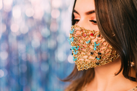 Covid-19 fashion. Pandemic Xmas. Quarantine party accessory. Profile portrait of sensual woman in ethnic style gold chain face mask on blue pink bokeh light blur tinsel copy space background.