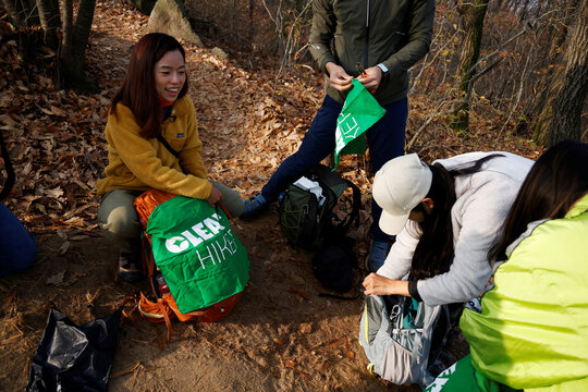 Kim Kang-Eun, a hiking artist who leads Clean Hikers, gets ready with her colleagues to collect litter while hiking, at a mountain in Incheon