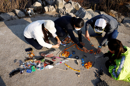 Members of Clean Hikers make an artwork with litter they collected while hiking on the peak of a mountain in Incheon, South Korea