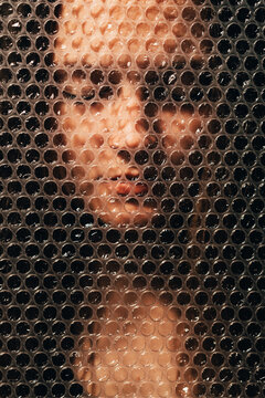 Peaceful woman. Female tenderness. Mind tranquility. Textured portrait of relaxed calm face with closed eyes behind dark plastic bubble wrap wall.