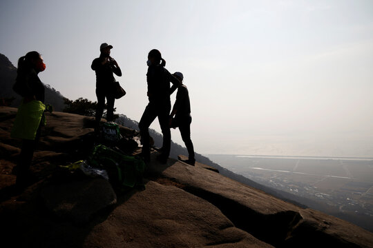Members of Clean Hikers rest as they collect litter while hiking near the peak of a mountain in Incheon, South Korea