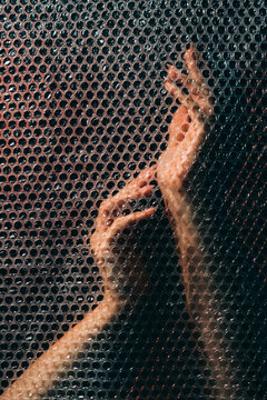 Hands art. Graceful performance. Spiritual practice. Freedom tranquility. Gentle sensual female arms behind transparent plastic bubble wrap texture wall in darkness.