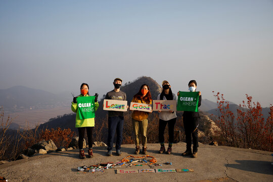 Kim Kang-Eun, an artist who leads Clean Hikers, and her colleagues pose with their artwork made from litter collected during their hikes, on the peak of a mountain in Incheon, South Korea