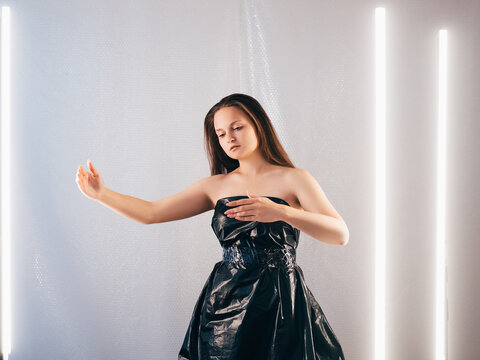 Plastic recycling. Waste reuse. Trash fashion. Ecology problem. Indifferent marionette doll woman dancing in black cellophane garbage bag dress on light bubble wrap copy space background.