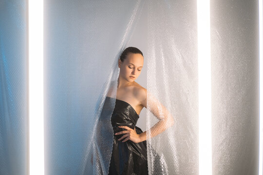 Covid-19 fashion. Pandemic self isolation. Stay safe. Social distancing. Sensual woman in black polyethylene dress posing behind protective bubble wrap drop curtain on light illuminated background.
