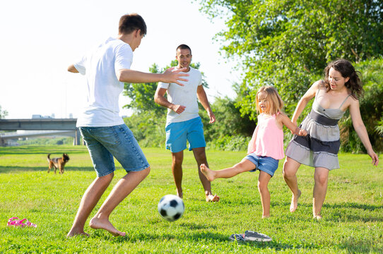 Group of smiling children and parents having fun together outdoors playing football. High quality photo
