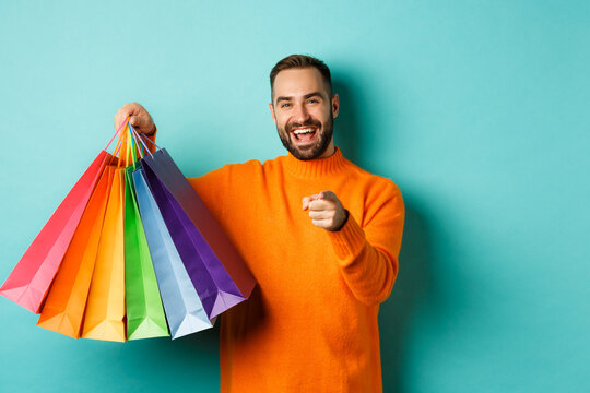 Happy adult man pointing finger at camera, holding shopping bags and smiling, standing over turquoise background