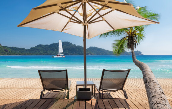 Sunny beach with umbrella and deckchairs on wooden floor, palm trees and a sailing boat in the turquoise sea on Paradise island.