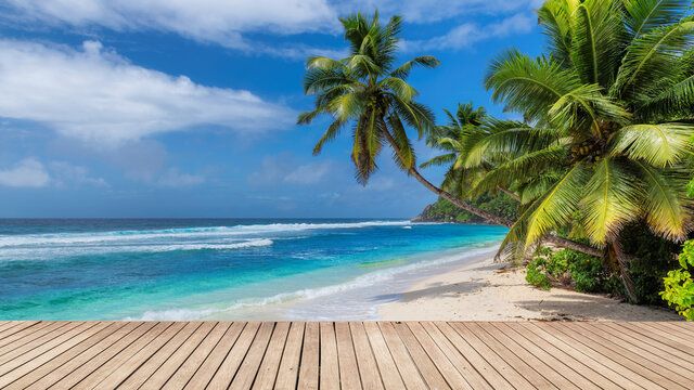 Paradise Sunny beach with wooden floor, palm trees and the turquoise sea on tropical island.