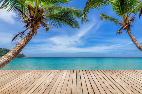 A wooden table product display with a summer vacation, holiday background of a tropical beach, blue sea, and green palm trees.