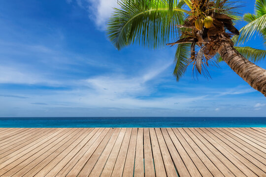 Tropical Sunny beach with wooden floor, palm trees and the turquoise sea on Paradise island.