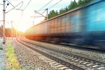 Motion blurred heavy cargo freight rusty train wagons moving on railway on sunset or sunrise day...