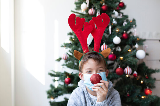 Boy with reindeer antlers and mouth nose mask sits in front of christmas tree and holds red christmas tree ball in front of his nose
