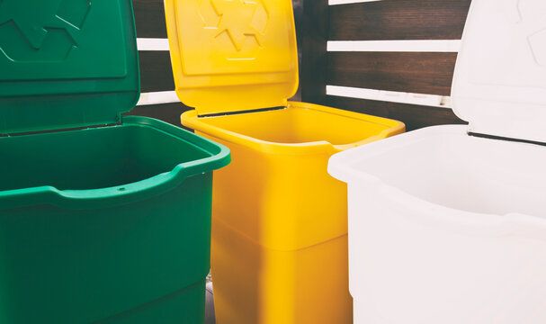 Three colorful trash cans for sorting garbage. For plastic, glass and paper
