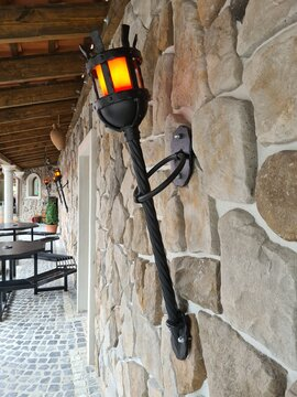 Ancient iron torch on concrete white wall outside
