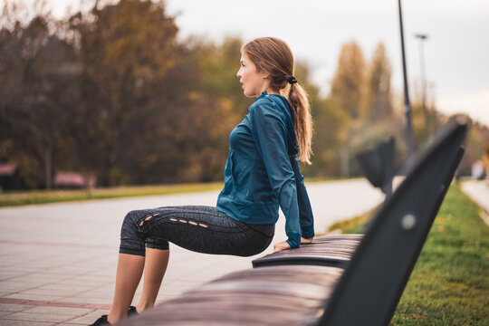 Beautiful adult woman is exercising outdoor on cloudy day in autumn. She is doing reverse push-ups.