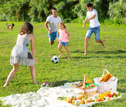 Positive parents with two kids playing soccer together on green field on summer day. High quality photo
