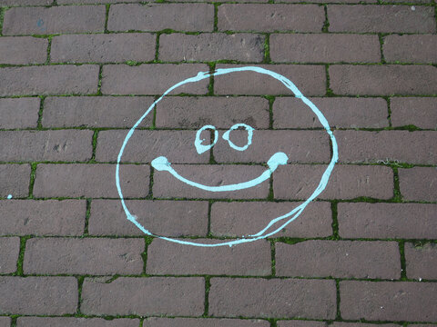green painted smile on a red brick sidewalk