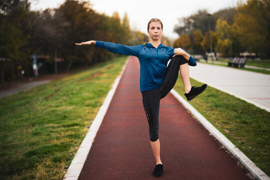 Beautiful adult woman is exercising outdoor on cloudy day in autumn.
