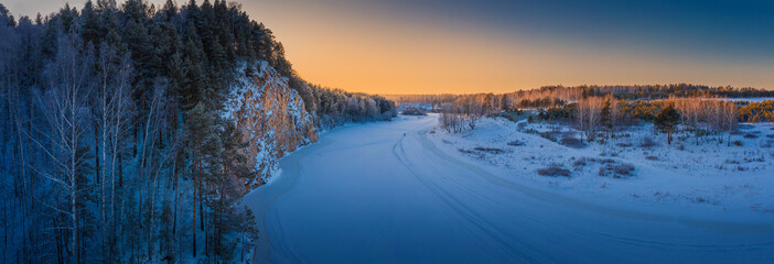 Fotobehang - Winter landscape. Sunset over mountain cliff and snowy river panorama.