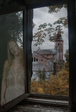 The Ghost of a girl is reflected in the window of an old abandoned house