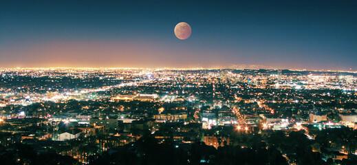 Fotobehang - Los Angeles skyline at night, full moon rising above illuminated cityscape. California, USA