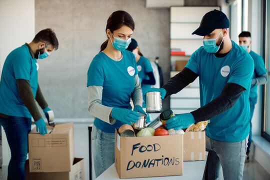 Volunteers wearing face masks while packing food in donation boxes for charity.