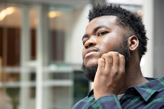 Man scratching suffering from itching facial skin; sick African man scratching his skin with allergy, rash, ringworm, tinea problem; skin care, dermatology concept; adult black African man model