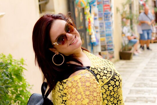 Portrait Of Cheerful Young Woman Wearing Sunglasses While Standing On Footpath
