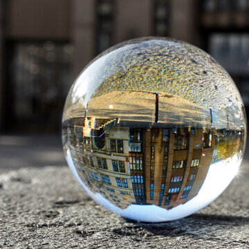 Crystal ball on a rough stone slab with the inverted spherically distorted image of a building in the city center