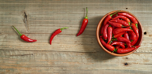 Red hot chili pepper with bowl on old wooden background.