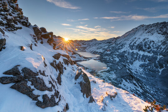 A tourist watches the sunset in the snow-capped winter Tatras