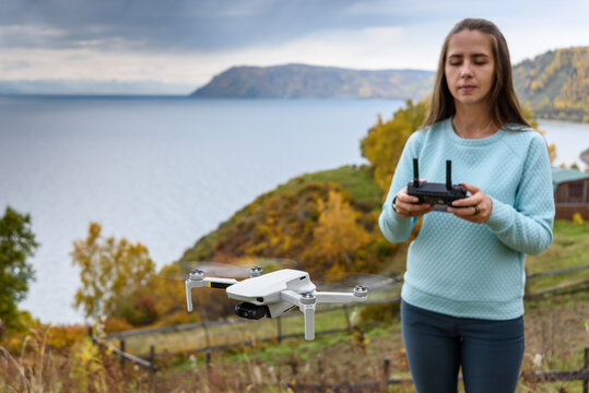 Blurry figure of girl controls a drone on autumn blurred background. Soft focus consept