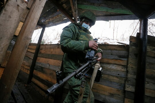 Donetsk People's Republic militant checks machine gun on a position located on the troops contact line with Ukrainian forces in Donetsk Region