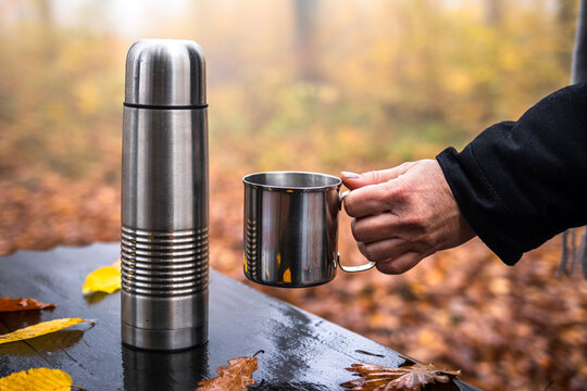 Woman holding cup, thermos with hot drink on table. Refreshment during hike in autumn woodland