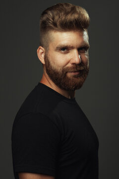 Fabulous at any age. Portrait of smiling 35-year-old man with fit body standing over gray background in black t-shirt. Hipster style. Red hair, modern haircut. Studio shot