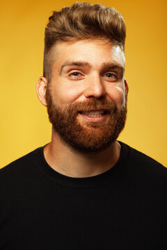 Fabulous at any age. Portrait of smiling 35-year-old man standing over yellow background in black t-shirt. Close up. Hipster style. Red hair, modern haircut. Studio shot
