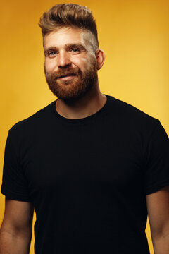Fabulous at any age. Portrait of smiling 35-year-old man with fit body standing over yellow background in black t-shirt. Hipster style. Red hair, modern haircut. Studio shot