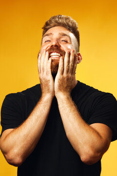 Portrait of happy, screaming for joy 35-year-old man with fit body posing over yellow background in black t-shirt. Hipster style. Red hair, modern haircut. Studio shot