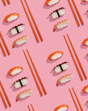 Pattern of sushis or niggiris with orange chopsticks over a pink background