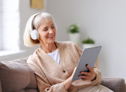 Cheerful senior woman using tablet and listening to music.