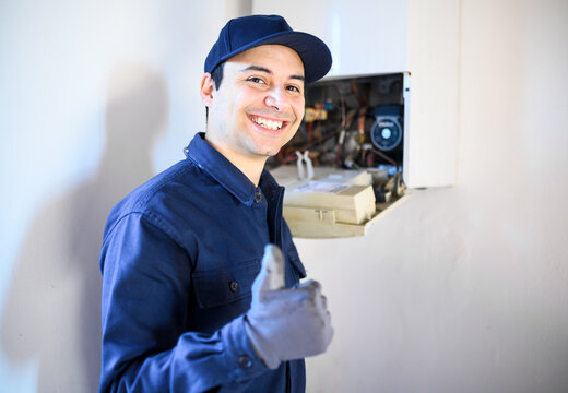 Smiling technician repairing an hot-water heater and showing thumbs up