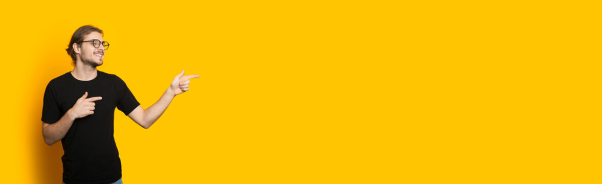 Handsome caucasian man with beard and eyeglasses pointing to the free space on a yellow wall