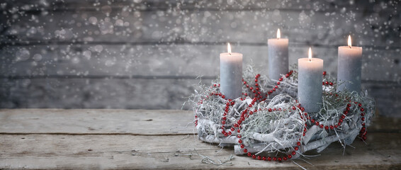 Advent wreath of white painted branches with burning candles and a red chain, tradition in the time before Christmas, rustic wooden background with snowy bokeh and copy space, panoramic format