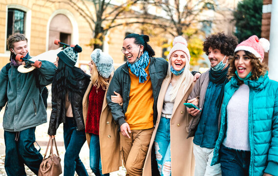 Milenial people walking and having fun together wearing open face mask at old town - New normal lifestyle concept with multicultural friends on winter fancy clothes - Focus on central part of frame
