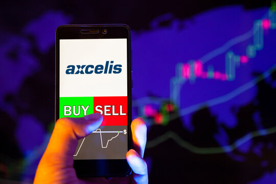 Company logo Axcelis Technologies, Inc. (ACLS) on smartphone screen, hand of trader holding mobile phone showing BUY or SELL on background of stock chart. Russia, Stavropol - May 29, 2019